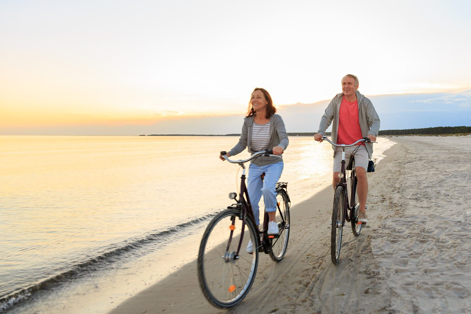 senior couple cycling on beach