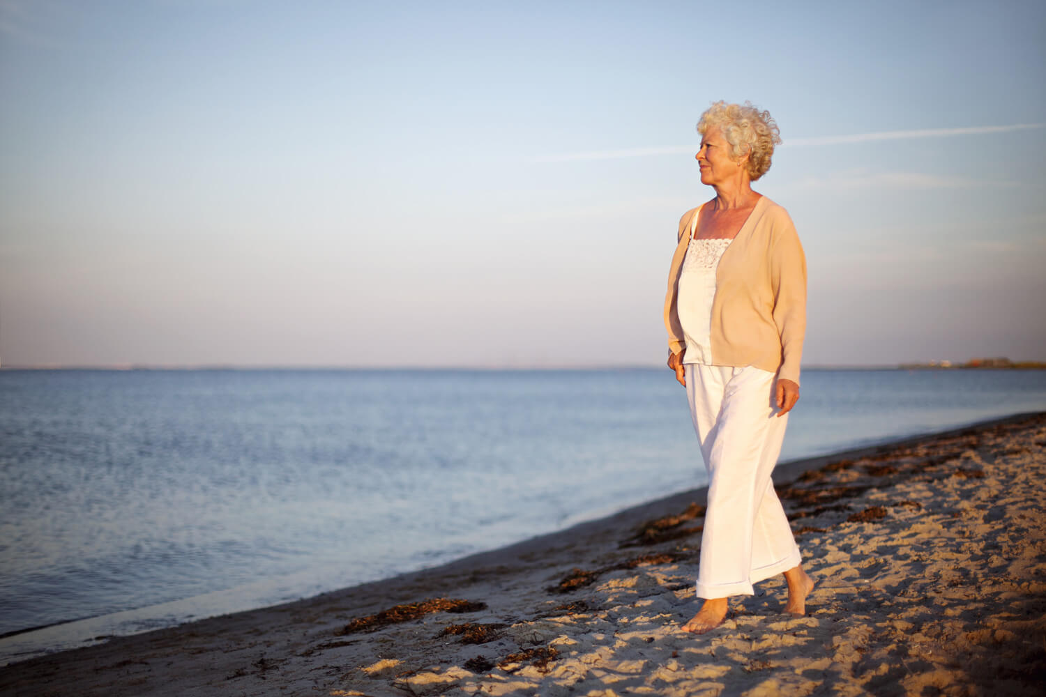 senior woman walking on beach